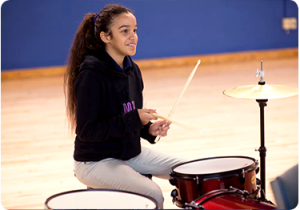 MusiCan student Ana playing the drums